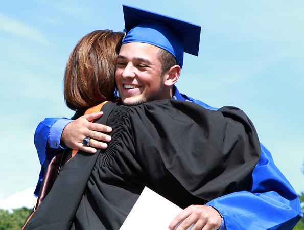 Danvers High School senior Michael Scarfo hugs Principal Susan Ambrozavitch after receiving his diploma on Saturday afternoon. David Le/Staff Photo