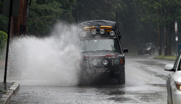 An SUV sprays water high in the air as it plows through a deep puddle on Humphrey St. in Swampscott on Wednesday afternoon. In addition to heavy rain and flash flooding, hail rained down on Swampscott and the area was issued a tornado warning. David Le/Staff Photo