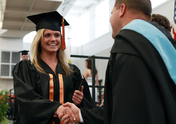 Beverly HIgh School senior Noelle Putur shakes hands with Beverly High School Principal Sean Gallagher after receiving her diploma on Sunday afternoon. David Le/Staff Photo