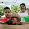 Phoenix Bettancourt, 6, of Beverly, picks out a few beets from a bucket under the watchful eye of his mother, Stephanie Bettancourt at the Beverly Boostraps Mobile Market on Tuesday afternoon. David Le/Staff Photo