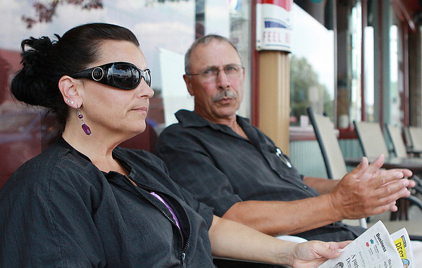 Danvers: Jennifer Little, left, and Frank Limoli, of Zollo's Barber Stylist in Danvers sit in the shade outside their shop and enjoy a beautiful July afternoon. Photo by David Le/Salem News