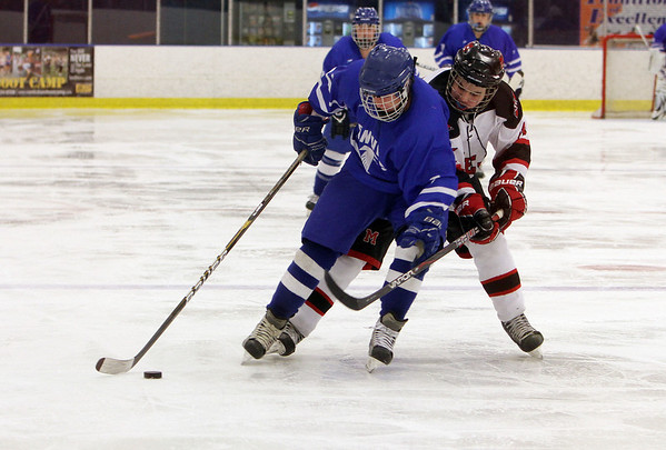 Danvers foward Matt Flynn, left, shields a Marblehead player as he carries the puck in the offensive zone. David Le/Salem News