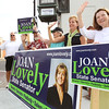 State Senate candidate Joan Lovely, second from right, waves to passersby in Danvers Square with her supporters on Saturday morning. David Le/Staff Photo