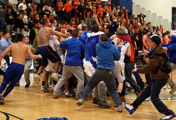 Danvers fans storm the court after the Falcons' pulled off a come from behind OT victory over Wayland on Tuesday night in Lawrence. David Le/Staff Photo