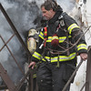 Peabody: With smoke still billowing behind him a Peabody firefighter climbs down the stairs. David Le/Salem News