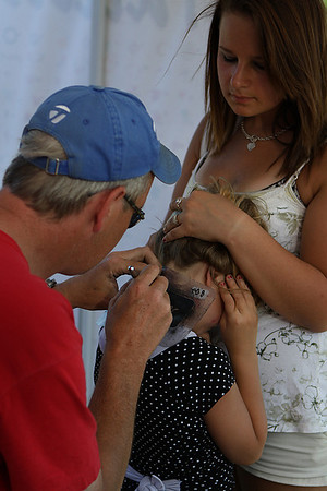 Danvers: Rhyan Foster, of Salem watches as her sister, Paige, 7, gets an airbrush pattern applied to the back of her neck by Chris Martikke of Danvers. Photo by David Le/Salem News