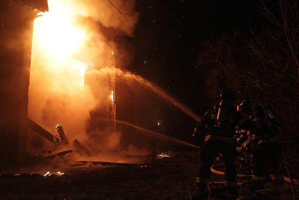 Firefighters from many local communities attempt to put out a heavy blaze that started on the backside of an apartment complex on Wednesday night. David Le/Salem News