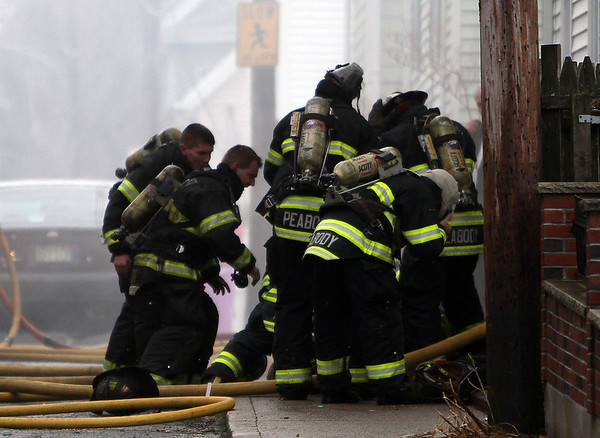 Peabody: Peabody firefighters hurry to carry firefighter Jim Rice out of a burning house at 5 Hancock St. on Friday afternoon. David Le/Salem News