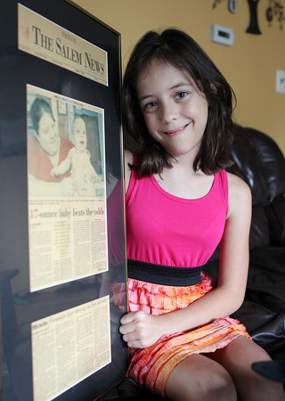 "Kaylyn Sverker, of Salem, was born prematurely at 1.1 pounds, but managed to ""beat the odds,"" and will turn 10 years old on Sunday. She is holding an article written in The Salem News nine years ago about her story. David Le/Staff Photo"