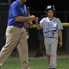 Danvers American runner Matt Reidy gets a congratulatory fist bump from Manager Jeff Smith after he reached third base against Andover on Friday evening.