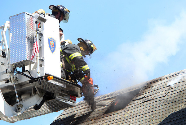 Peabody firefighters Bob Caruso, left, and Mike Eliuk, right, cut a ventilation hole in the roof of 20 Endicott St. while trying to combat a blaze on Wednesday afternoon. David Le/Staff Photo