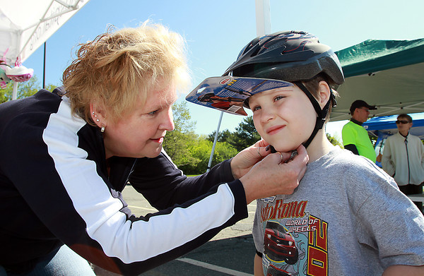 Carol McCullough, left, fits Justin Leedham, 7, of Danvers for a new bike helmet in the Liberty Tree Mall parking lot during the Danvers Kiwanis Club Bike Rodeo on Saturday morning. The Kiwanis Club and Beverly Hospital joined forces to raise awareness for bicycle-related injuries. There was a skills course, bike and helmet fittings, safety testing stations and free bike helmets for participating. David Le/Staff Photo