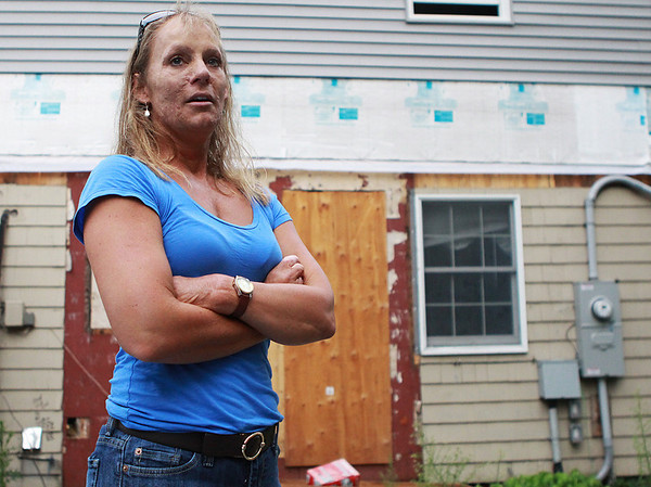 Danvers: Robin Kellow, of Danvers, stands just in front of the area where a tree fell on her house, completely demolishing the bathroom and causing terrible damage to the rest of her house as well as the pool. In the past year Kellow was struggled with insurance adjusters, her insurance company, the historic district commission and a fire that destroyed the temporary housing unit she and her twin sons were living in. Photo by David Le/Salem News