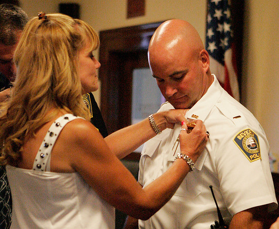 Beverly: Beverly Police Officer Lt. Joseph Shairs, has his badge pinned on his collar by his wife Jayne Shairs in a ceremony for the promotions of Lt. Joseph Shairs, Sgt. David Faustino, and Sgt. Richard Russo on Tuesday evening at Beverly City Hall. Photo by David Le/Salem News