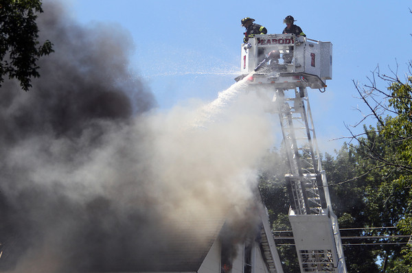 Thick smoke billows from a house on Endicott St. in Peabody as Peabody firefighters Bob Caruso and Mike Eliuk spray water from the basket of Peabody Ladder 1. David Le/Staff Photo