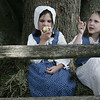 Dressed in period clothing, Niamh Sullivan, 8, of Marblehead and Sarah Newhall, 7, of Salem, rest on a bail of hay to eat a snack while at Glovers Regiment encampment at Fort Sewall this weekend. Photo by Deborah Parker/July 11, 2009
