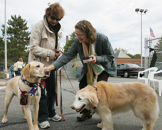 Susanna Brennan watches at Reverand Annika Kleschinsky of Heartlight Peace Ministires of Swampscott blesses her two dogs Gordy and Gemma during the Northeast Animal Shelter's Blessing of the Animals event Saturday. Photo by Deborah Parker/October 10, 2009