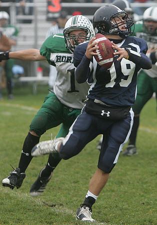 North Shore Tech's Dave St. Pierre releases the ball just before being tackled by Manchester Essex's Ben Kekeisen during Saturday's game held in Middleton. Photo by Deborah Parker/October 24, 2009