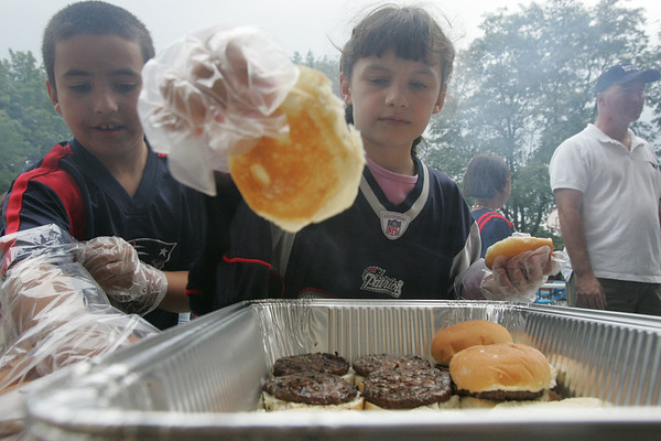 Fourth grade students at the Horace Mann School in Salem, Kevin Santa Cruz and Maddie Mazuzan, help to prepare hamburgers at the school's cookout Thursday evening to celebrate the start of school and the new principal Kevin Andrews. Photo by Deborah Parker/September 16, 2010