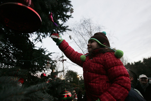 Cassie Giordano, 6, of Lynnfield gets some help from her dad, Joseph, to hang ornament on a tree as part of a Holiday Candlelight Service at Puritan Lawn Memorial Park in Peabody Sunday afternoon. photo by deborah parker/decemebr 5, 2010