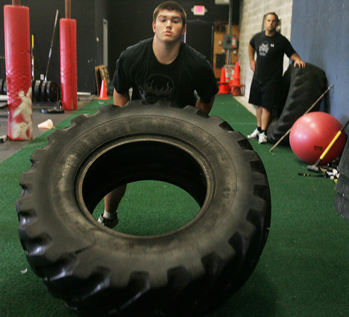 "Zach Nardone, a member of the Bishop Fenwick football team, practices a drill with a tire as part of ""gridiron training"" with athletic trainer Pat Downey.  Downey has started his own business working with many local high school players and teams. He is focusing on hardcore performance with individuals and specific teams. He previously served as a pro football strength and conditioning coach. Photo by Deborah Parker/September 30, 2009"