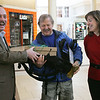 "Johnny Wowk of Peabody, also known as ""Johnny the Walker"", was celebrated at the North Shore Mall after reaching the  20,000 mile mark. He's been walking daily for years. Here, Mark Whiting, general manager of the North Shore Mall and Susan Ford of Lahey Clinic, which sponsers the walking program at the mall, give several gifts to Wowk including a new pair of walking sneakers and a backpack.  Photo by Deborah Parker/February 12, 2010"