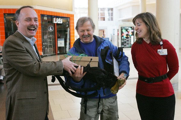 """Johnny Wowk of Peabody, also known as """"Johnny the Walker"""", was celebrated at the North Shore Mall after reaching the  20,000 mile mark. He's been walking daily for years. Here, Mark Whiting, general manager of the North Shore Mall and Susan Ford of Lahey Clinic, which sponsers the walking program at the mall, give several gifts to Wowk including a new pair of walking sneakers and a backpack.  Photo by Deborah Parker/February 12, 2010"""