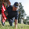 Arnold Doucette of Beverly, a veteran of the Korean War, places a flag at a gravestone in Central Cemetary Wednesday evening in honor of the upcoming Memorial Day holiday. A group of veterans worked to place flags around town. Photo by deborah parker/may 26, 2010