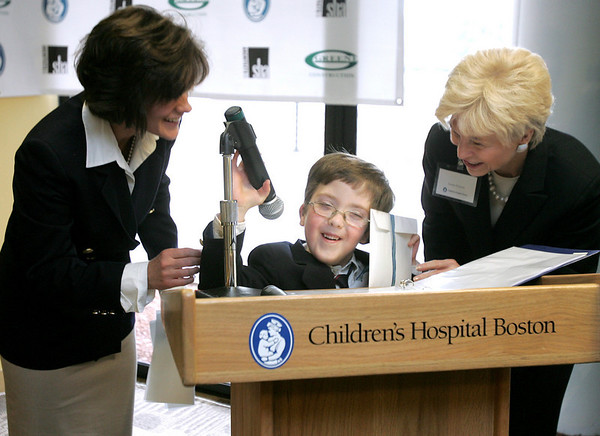 Sandra Fenwick, President and Chief Operating Officer of Children's Hospital Boston, right along with Laurie Blake and her son Kevin, a patient with Children's play at the podium following a presentation at the new location of Boston Children's North. Photo by Deborah Parker/January 28, 2010