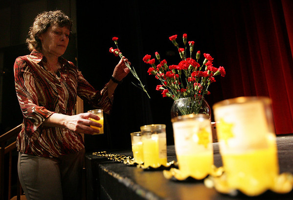 Sandy Weitz of Peabody, daughter of Sonia Weitz, places a flower and candle on the stage during Day After Night, the Holocaust Center Boston North's annual interfaith commemoration of the genocide, held at Peabody Veterans Memorial High School Monday evening. Photo by Deborah Parker/April 12, 2010