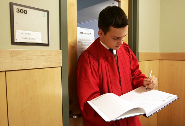Alex Bogart of Boxford signs a yearbook while waiting at his homeroom before marching to the field house for the graduation ceremony at Masconomet Regional High School Friday evening. Photo by Deborah Parker/June 5, 2009