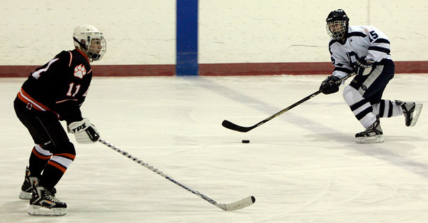 Peabody: Peabody's Rob Houghton brings the puck down the ice against Beverly's Mitch Hamor during Saturday's season opener held at McVann-O'Keefe Rink. Photo by Deborah Parker/Salem News Saturday, December 13, 2008.