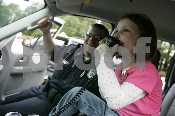 Danvers: With the help of Officer Joseph Grodin from the Nahant Police Department, Emma Guthrie, 5, of Danvers, yells hello over the police vehicles loud speaker during Truck Day at Endicott Park Saturday. The event, which was sposered by the town Recreation Department featured vehicles covering police motorcycles to school buses, to cement trucks.<br /> Photo by Deborah Parker/Salem News Saturday, September 13, 2008