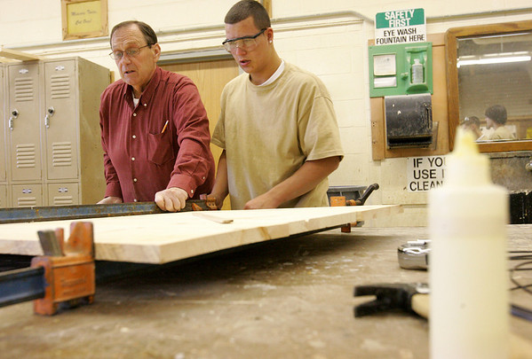 Carpentry teacher John Eaton works with student Mike Gauthier on the base of a Christmas decoration during class at the Peabody High Vocational School located inside Higgins Middle School. Photo by Deborah Parker/November 17, 2009