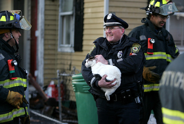 Patrolman Rick Heath is all smiles after rescuing a cat that ran back inside a buring home at 30 Harris Street in Peabody yesterday afternoon. Photo by Deborah Parker/January 26, 2009