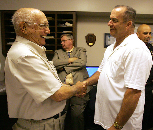 Retiring Salem police captian John Jodoin is congratulated by former custodian of the Salem Police Station, Neo Rizzotti of Salem, during a ceremony and luncheon at the station in Jodoin's honor in Salem Wednesday afternoon. Photo by Deborah Parker/June 30, 2010