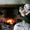 Reenactor Kathryn Rutkowski of Salem sits by the fire Sunday morning while at the Rebecca Nurse homstead. The Danvers Alarm List Company hosted The Battle of Crane Brook, a celebration of 18th century colonial life this weekend at homestead. Photo by Deborah Parker/October 4, 2009