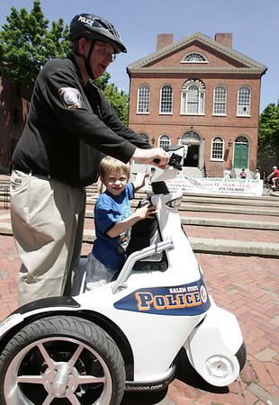 Salem State College Police Chief, William Anglin takes his grandson, Ryan Corneau, 5, of Amesbury for a spin on the T3 and electric vehicle in front of the Old Town Hall in Derby Square as part of the Living Green and Renewable Energy Fair at the Hall Saturday. The Salem State College police as well as Salem Police have two of these vehicles which are useful in downtown and campus areas. Photo by Deborah Parker/June 13, 2009