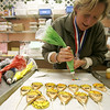 Kelly Delaney, owner of Cakes For Occasions, creates Olympic rings made of out frosting that will decorate an Olympic themed cup cake. Now through February 28th, for every $5 you spend on Olympic themed pastries at the shop you can get a ticket to be entered to win a snowboard, passes to Shawnee Peak or a $50 gift certificate to Cakes for Occasions. Photo by Deborah Parker/February 9, 2010