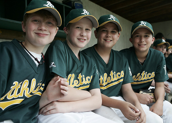 From left, Athletics teammates, Alex Tisi, 12, Jacob Laflam, 12, Myles Tennihan, 12, and Christian Kukas, 10, all of Peabody pose together while sitting in the duggout during their Little League game against the Diamondbacks at Cy Tenney Park Sunday afternoon. Photo by Deborah Parker/May 31, 2009