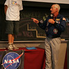 Junior Martinez, 13, of Salem, along with Jeff Hoffman, professor at MIT and former astronaut, demonstrates how gravity works in space by jumping off a table while at MIT on Thursday. Students from Massachusetts including Salem were invited to MIT to watch a live feed from the Interantional Space Station to watch as robots they programmed compete in a race in space.  Photo by Deborah Parker/August 19, 2010
