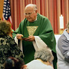 Father Herbert Jones gives communion at the Carmelite Chapel-in-the-Mall at the North Shore Mall Tuesday afternoon. Photo by Deborah Parker/October 27, 2009