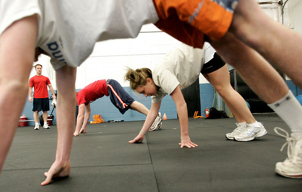 Topsfield: Matt Foley, owner of a sports and fitness conditioning gym on Route 1 in Tospfield, oversees a floor excersize while at the gym. From left are high school students, Jack Hoesly, 16, from Masco, Mackenzie Grenert, 16, from Hamilton-Wenham and Connor Brown, also from Masco.  Photo by Deborah Parker/Salem News Thursday, February 26, 2009.