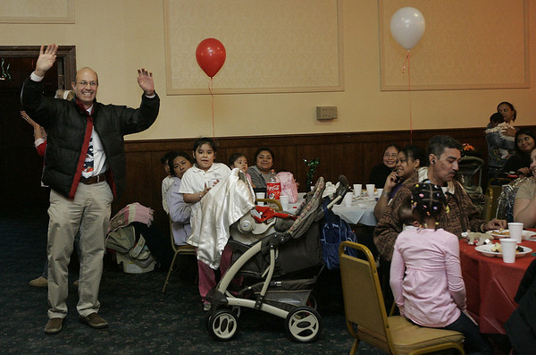 Lynn: Beverly physician, Doctor Luis Laz waves to the crowd attending his annual Baby's First Christmas Party. Laz holds the party to give back to patients and their families providing a lunch, pictures with Santa and a raffle. This year Laz was honored by the city of Lynn for his commitment and genorsity towards the community. Photo by Deborah Parker/Salem News Friday, December 05, 2008