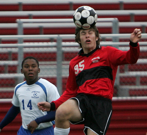 Marblehead's Sam Terrill heads the ball against O'Bryant's Aruna Bah during yesterday's game held at Marblehead High School. Photo by Deborah Parker/October 8, 2009