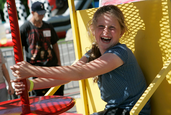 Kaitlin Karnachuck, 9, of North Andover is all smiles as she spins on a ride during the Danvers Family Festival before the annual fireworks Sunday evening. The festival included a dj, food, rides, games and bouncy houses. Photo by Deborah Parker/July 5, 2009.