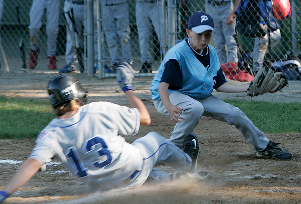 Danvers American Bailey Klein slides safely into home against Peabody American pitcher, Matt Moorer during Sunday afternoon's District 15 Little League All-Star game. Photo by Deborah Parker/July 5, 2009.