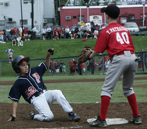 Peabody West's Matt Correale slides safely into third against North Andover's Todd Patnaude during Friday night's game held at Wyoma Field in Lynn. Photo by Deborah Parker/July 24, 2009