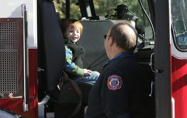 Call fire fighter John Morris talks to Toby Stewart, 2, of Ipswich about how a fire truck works while at the Ipswich Fire Station during their open house Saturday morning. Photo by Deborah Parker/October 9, 2010
