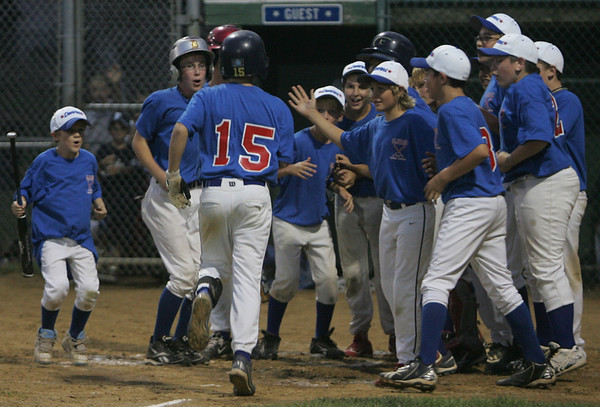 Danvers' Andrea Olszak is greeted at home plate by his teammates after hitting a home run during yesterday's Gallant Memorial Baseball tournament game against Peabody held at Forest River Park in Salem. Photo by Deborah Parker/August 16, 2010